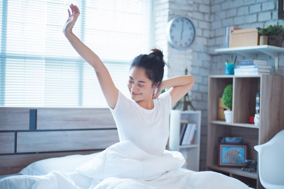 woman waking up refreshed after getting 3 health benefits for using her AC while sleeping