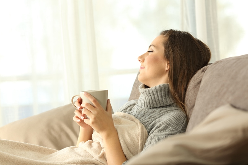 Portrait of a pensive woman relaxing sitting on a sofa in the living room in a house interior in Portland, enjoying her zone control system