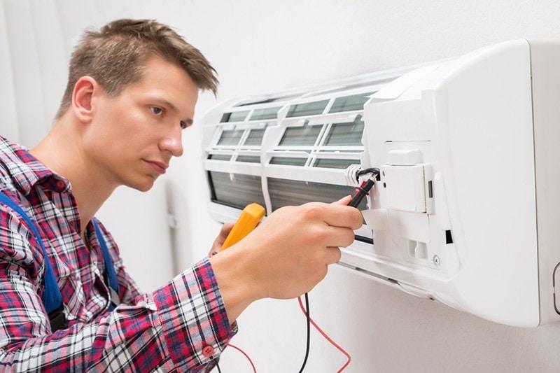 man fixing a HVAC unit