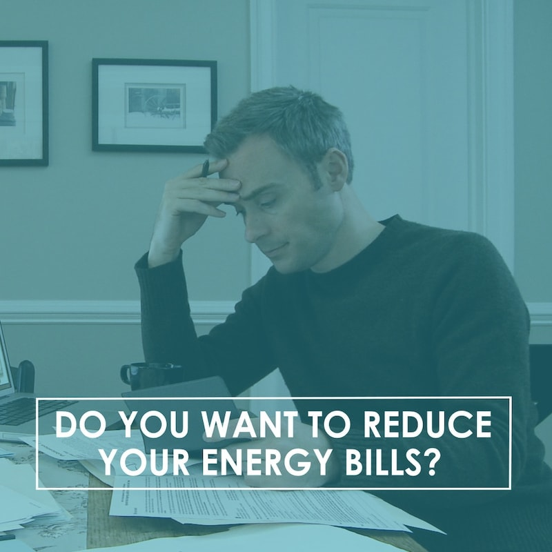 Dop you want to reduce your energy bills? Man sitting at a desk looking at his bills.