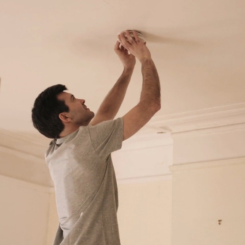 Man changing the batteries on his smoke detector.