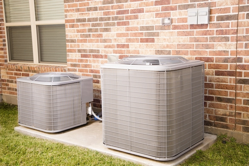 Two air conditioner units outside brick home.