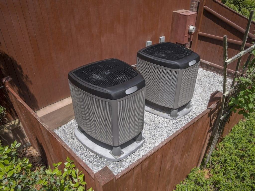 Residential heating and air conditioner compressor units near residential house|Calculator & money
