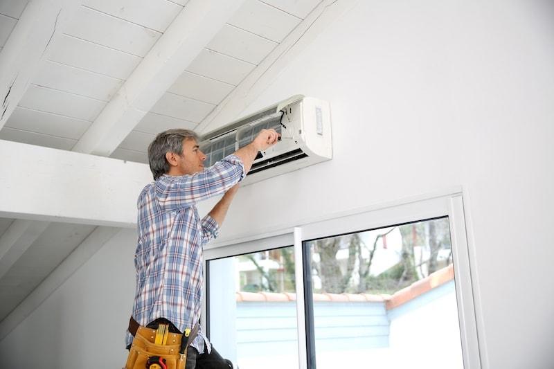 Man performing ductless maintenance.