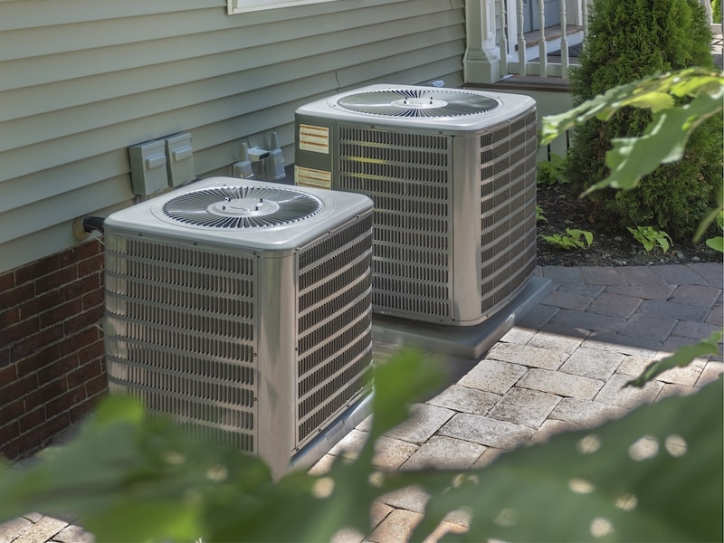 2 air conditioning units outside.|Smiling technician servicing a hot-water heater